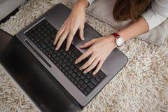Ładna brunetka używać laptop na podłoga Fotografia Stock