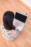 Ładna brunetka używać laptop na podłoga Obraz Royalty Free