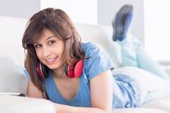 Ładna brunetka używać pastylka komputer osobistego na leżance Zdjęcie Royalty Free