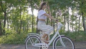 Ładna brunetka w białej spódnicie, bluzka jedzie miasto rower wzdłuż ścieżki w parku i bierze daleko jej słomianego kapelusz i zbiory wideo