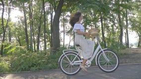 Ładna brunetka w białej spódnicie, bluzka jedzie w słońcu na białym miasto rowerze wzdłuż ścieżki w parku, bierze zbiory