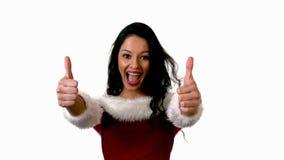Ładna brunetka w Santa stroju pokazuje aprobaty zbiory
