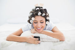 Ładna brunetka w włosianych rolownikach kłama na jej łóżkowym dosłaniu tekst Obraz Stock