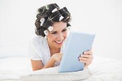Ładna brunetka w włosianych rolownikach kłama na jej łóżku używać jej stół Zdjęcia Royalty Free