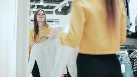Ładna brunetka wybiera bluzkę w sklepie Młoda uśmiechnięta kobieta sprawdza na pulowerze w sklepie odzieżowym patrzeje w lustro zdjęcie wideo