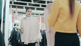 Ładna brunetka wybiera między dwa bluzkami Młody uśmiechnięty kobiety sprawdzać odziewa w sklepie patrzeje w lustro Moda zbiory
