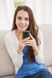 Ładna brunetka wysyła tekst na leżance Obrazy Stock