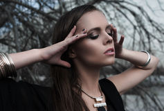 Ładna brunetki dziewczyna jest ubranym czarny pozować outdoors na błękitnym lata niebie z jaskrawym makeup i purpurowymi wargami  Obrazy Royalty Free