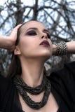 Ładna brunetki dziewczyna jest ubranym czarny pozować outdoors na błękitnym lata niebie z jaskrawym makeup i purpurowymi wargami  Obraz Royalty Free