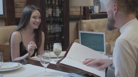 Ładna brunetki kobieta pije koktajlu obsiadanie przy stołem z jej brodatym chłopakiem słucha on i ono uśmiecha się zbiory