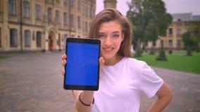 Ładna caucasian dziewczyna patrzeje prosto z zaufaniem swiping jej pastylkę i wtedy pokazuje błękitnego ekran przy kamerą, miasto