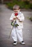 Ładna chłopiec chwyta czerwieni róża w ręce Zdjęcie Stock