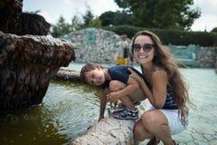 Ładna chłopiec z matką bawić się blisko fontanny plenerowej zdjęcie royalty free