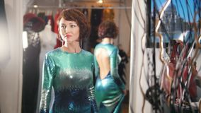 Ładna czerwona z włosami kobieta w zielonej wieczór sukni pozuje w lustrze w butik sala wystawowej zdjęcie wideo