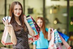 Ładna dama pokazuje kredytową kartę w centrum handlowym Obrazy Royalty Free
