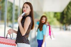 Ładna dama pokazuje kredytową kartę w centrum handlowym Zdjęcia Stock
