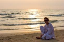 Ładna dama przy plażowym wydatki zmierzchu czasem Fotografia Stock