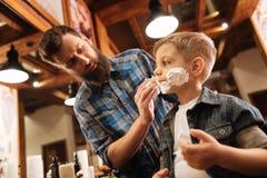 Ładna dobra przyglądająca fryzjera męskiego kładzenia piana na chłopiec stawia czoło Obraz Stock