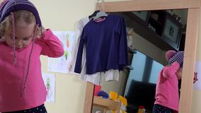 Ładna dziecko dziewczyny różnorodnych ciepłych kapeluszy przed lustrem miara w domu zbiory wideo