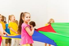 Ładna dziewczyna bawić się spadochron z jej przyjaciółmi obrazy royalty free