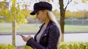 Ładna dziewczyna chodzi na alei i opowiada na telefonie zbiory