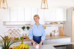 Ładna dziewczyna chodzi w kuchnię i rozciągliwość cieszy się ranek c, zdjęcia stock