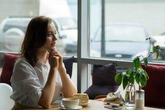 Ładna dziewczyna cieszy się fragrant kawy i cukierki tortowego obsiadanie w kawa domu Biznesowa kobieta odpoczywa podczas przerwy Zdjęcie Royalty Free