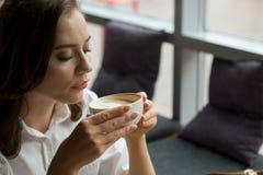 Ładna dziewczyna cieszy się fragrant kawy i cukierki tortowego obsiadanie w kawa domu Biznesowa kobieta odpoczywa podczas przerwy Fotografia Royalty Free