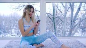 Ładna dziewczyna cieszy się melodie i potrząśnięcia przewodzą w rytmu siedzi blisko okno w pokoju zbiory wideo