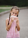 Ładna dziewczyna je cheeseburger na zamazanym ulicznym tle Troszkę dziewczyna z kanapką Obrazy Royalty Free