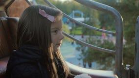 Ładna dziewczyna jedzie na carousel, ono uśmiecha się ale spojrzenia męczący z jej misiem pluszowym przy zmierzchem w mo zbiory wideo