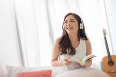 Ładna dziewczyna jest roześmiana i trzymająca książkę w białym pokoju zdjęcia stock
