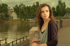 Ładna dziewczyna jest ubranym czarną koszula, stoi przeciw ogrodzeniu Volga rzeką w Karakułowym w lecie, przyglądającym z powrote zdjęcie royalty free
