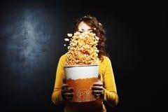 Ładna dziewczyna ma zabawę przy kino popkornu potrząsalnym wiadrem fotografia stock