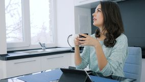 Ładna dziewczyna marzy podczas gdy pijący herbaty z pastylką w kuchni zbiory wideo