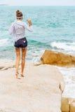 Ładna dziewczyna na dużym kamieniu przy plażą Obraz Royalty Free