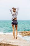 Ładna dziewczyna na dużym kamieniu przy plażą Zdjęcia Stock