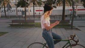 Ładna dziewczyna na jej miastowym rocznika bicyklu przy zmierzchem zbiory