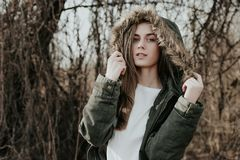 Ładna dziewczyna pozuje na kamerze w ciepłej zielonej kurtce z futerkowym kapiszonem Fotografia Royalty Free