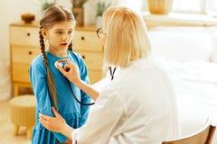 Ładna dziewczyna stoi cicho podczas gdy pediatra egzamininuje jej płuca zdjęcie stock