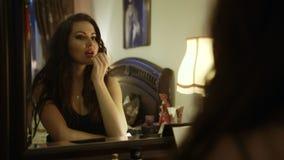 Ładna dziewczyna stosuje czerwoną pomadkę jej wargi podczas gdy patrzejący w lustrze, zbiory