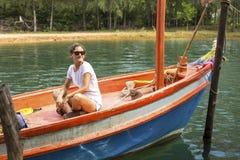 Ładna dziewczyna turystyczny obsiadanie w autentycznej Tajlandzkiej łodzi rybackiej hobby Obraz Stock
