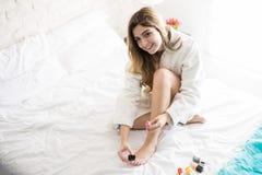 Ładna dziewczyna używa gwoździa połysk Zdjęcia Royalty Free