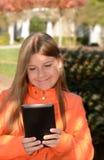 Ładna dziewczyna używa jej pastylkę Zdjęcia Royalty Free