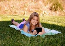 Ładna dziewczyna używa jej pastylkę Zdjęcia Stock