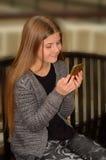 Ładna dziewczyna używa jej telefon komórkowego Zdjęcia Royalty Free