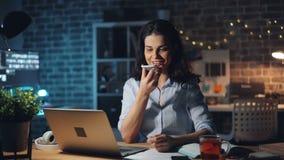 Ładna dziewczyna używa smartphone nagrania głosu wiadomość pracuje w biurze przy nocą zbiory