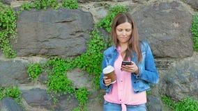 Ładna dziewczyna w bawełnianej kurtce używać smartphone i pijący kawę Rocznik ściana dziki kamień w tle zdjęcie wideo