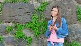 Ładna dziewczyna w bawełnianej kurtce używać smartphone z słuchawkami Rocznik ściana dziki kamień w tle zdjęcie wideo