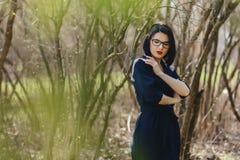 ładna dziewczyna w czarnym kostiumu wśród krzaków Fotografia Royalty Free